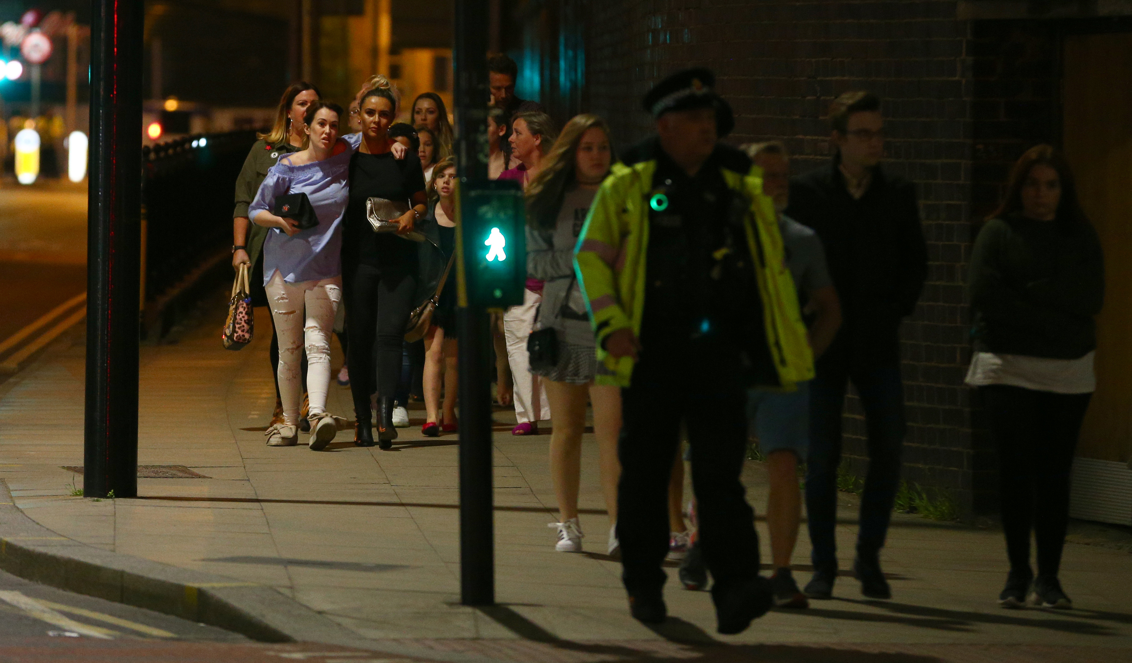 Police escort concert goers from the site of the Ariana Grande concert following a terror attack.