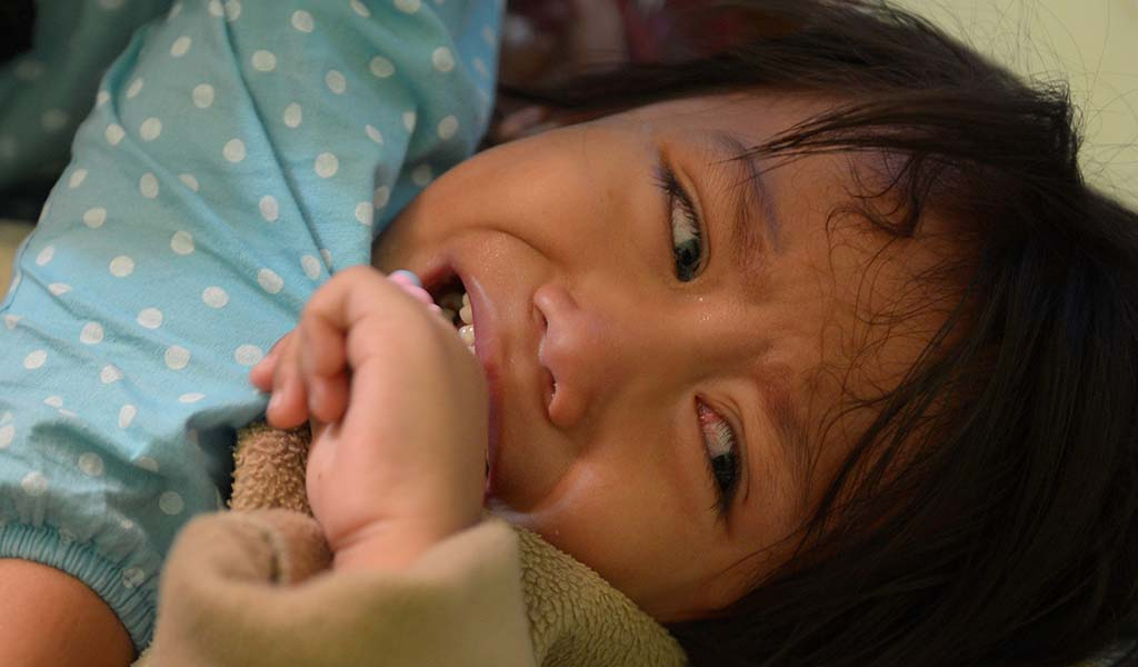 A young Indonesian girl cries as she undergoes FGM.