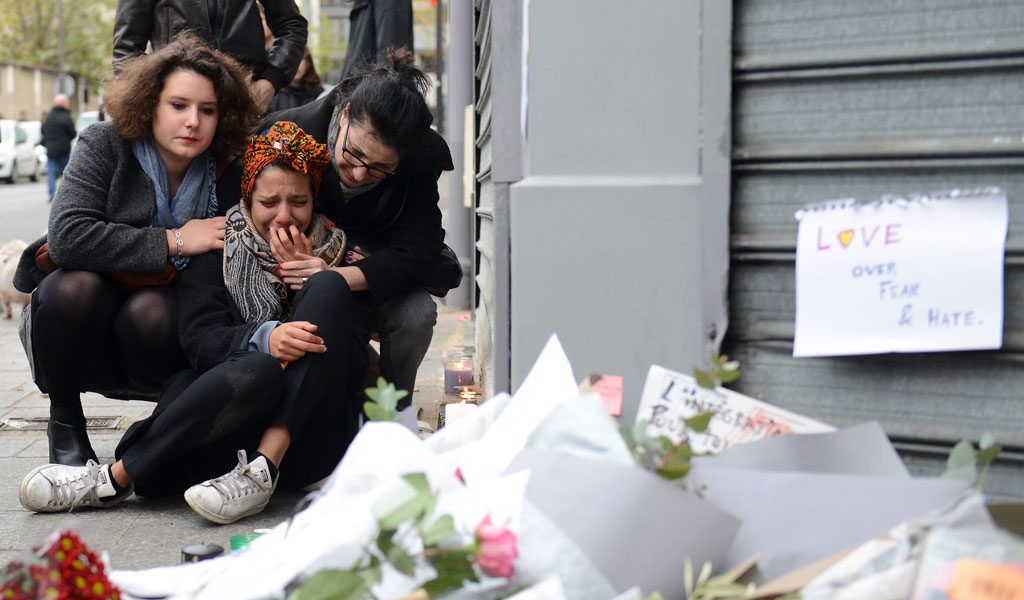 Young women mourn victims of the November 2015 terror attacks in Paris