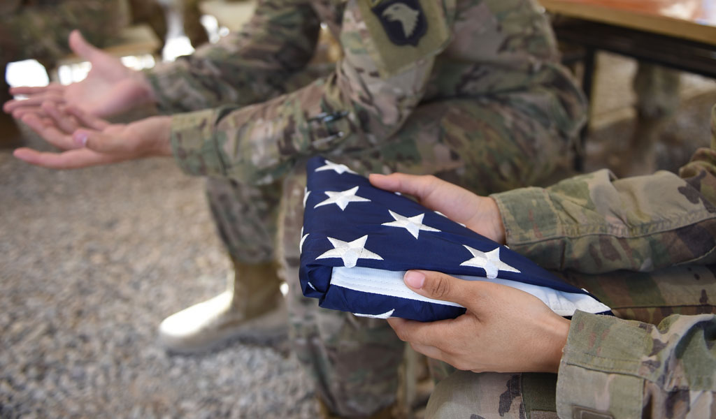 A US soldier holds the national flag ahead of a handover ceremony at Leatherneck Camp in Lashkar Gah in the Afghan province of Helmand on April 29, 2017.