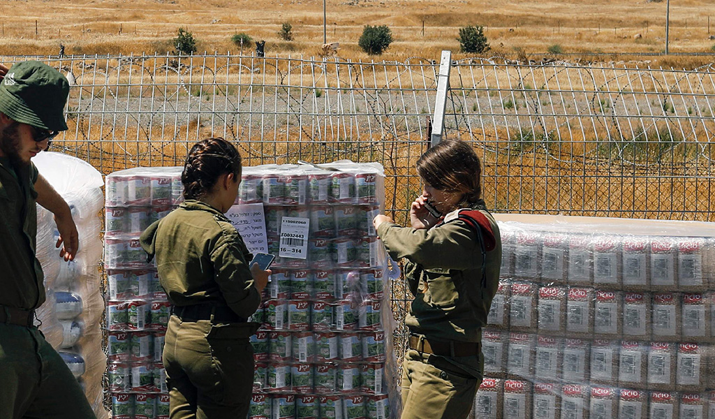 Israeli soldiers stand next to food supplies being prepared for Syrian IDPs. Israel is planning for a new field hospital to treat patients from the civil-war hit country.