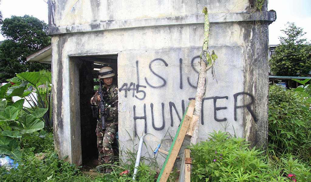 This photo taken on July 12, 2017 shows a Philippine soldier taking cover during an advance to the frontline where they are battling ISIS in Marawi on the southern island of Mindanao.