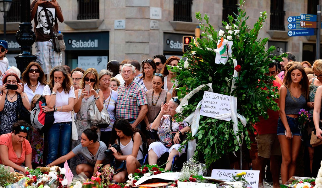Mourners gather around a makeshift memorial to the terror victims in Barcelona