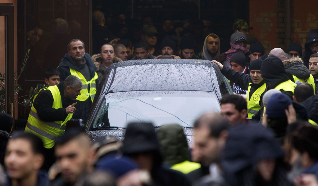 Muslim mourners and security guards surround the car bringing Omar El-Hussein, a terrorist who killed two people in two attacks in Copenhagen, for burial.