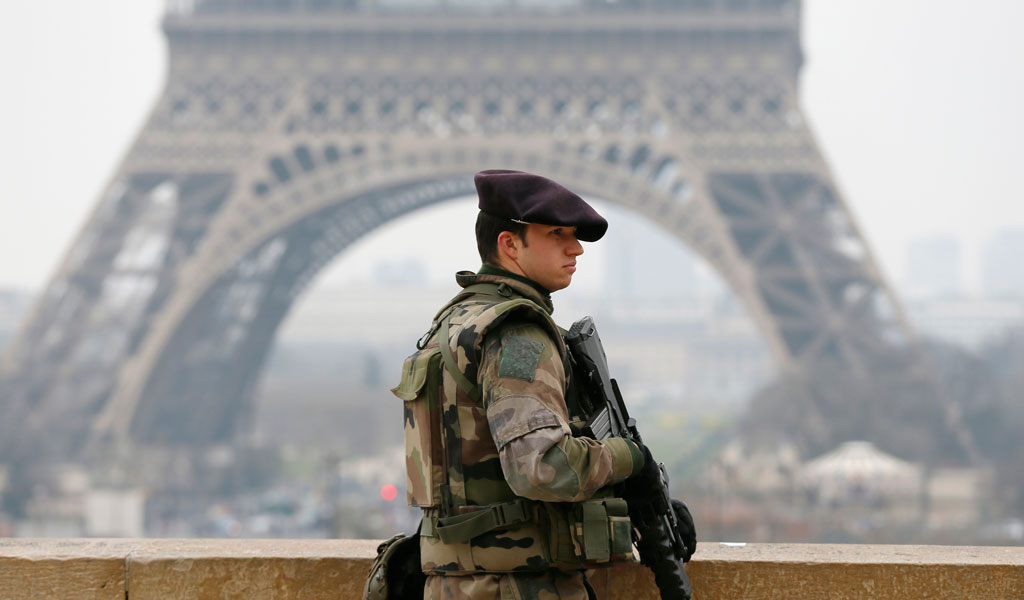 A French soldier stands guard close to the Eiffel Tower