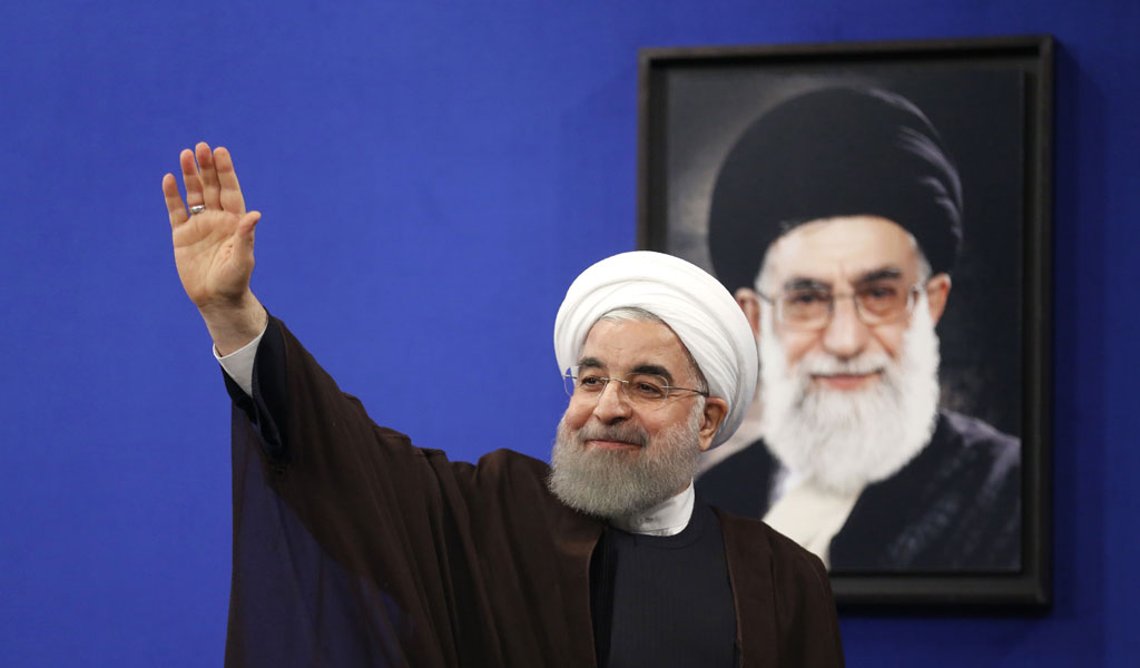 Iranian President Rouhani waves from under a picture of Supreme Leader Ayatollah Khamenei
