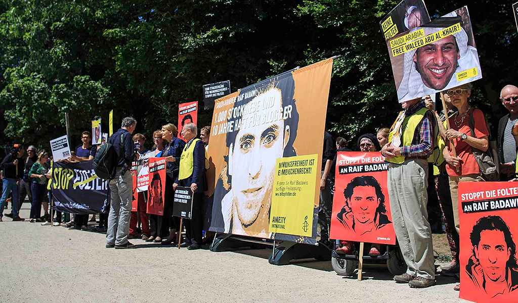 Activists hold banners as they demonstrate outside the Saudi Arabian Embassy against the recent Saudi court ruling that upheld a previous verdict of ten years in prison and 1,000 lashes for Saudi blogger Raif Badawi on June 11, 2015 in Berlin, Germany.