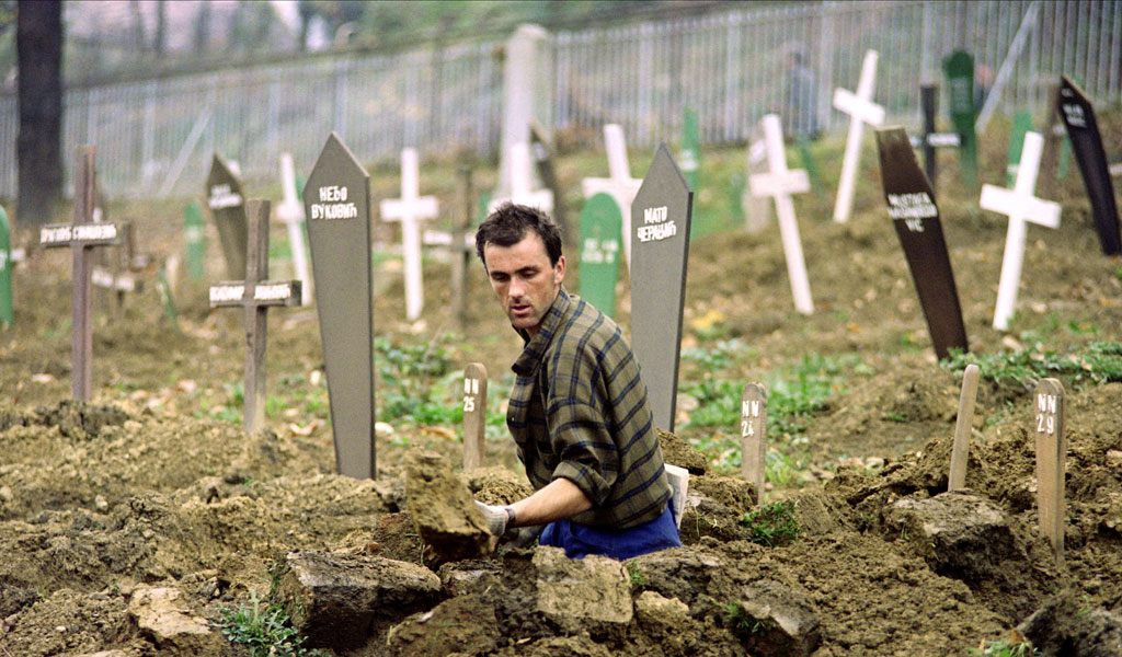 A worker in a cemetery for Christians and Muslims in Bosnia