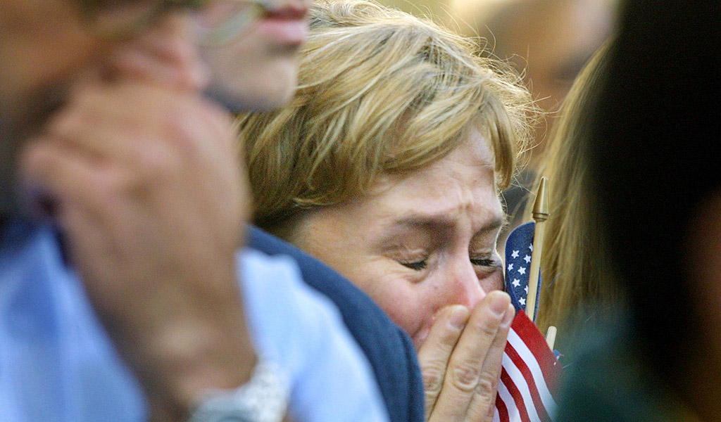 """A mourner cries while clutching a """"stars and stripes"""" flag during the remembrance service at St. Paul's Cathedral in London 14 September 2001."""