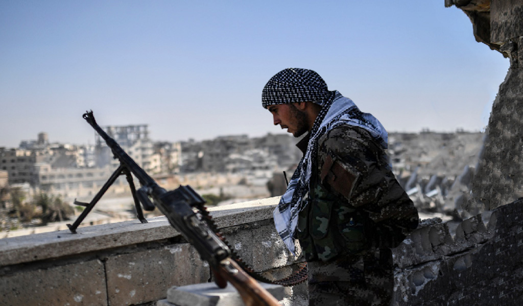 A fighter of the Syrian Democratic Forces (SDF) stands guard on a rooftop in Raqa on October 20, 2017, after retaking the city from Islamic State (IS) group fighters. SDF fighters flushed jihadist holdouts from Raqqa's main hospital and municipal stadium, wrapping up a more than four-month offensive against what used to be the inner sanctum of ISIS's self-proclaimed 'caliphate,' which for three years saw some of the group's worst abuses and grew into a center for both its potent propaganda machine and its unprecedented experiment in jihadist statehood.
