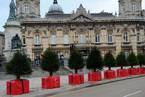 Security barriers in the UK made to look like Christmas trees on top of gift packages.