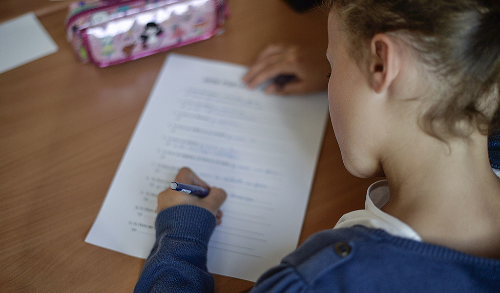 Illustrative picture of a pupil writing in school.
