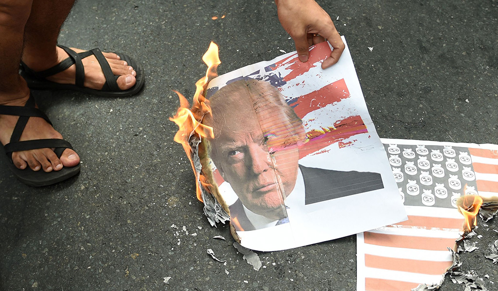 Filipino students burn a mock US flag and a photo of US President-elect Donald Trump during a rally in front of the US embassy in Manila on November 10, 2016.
