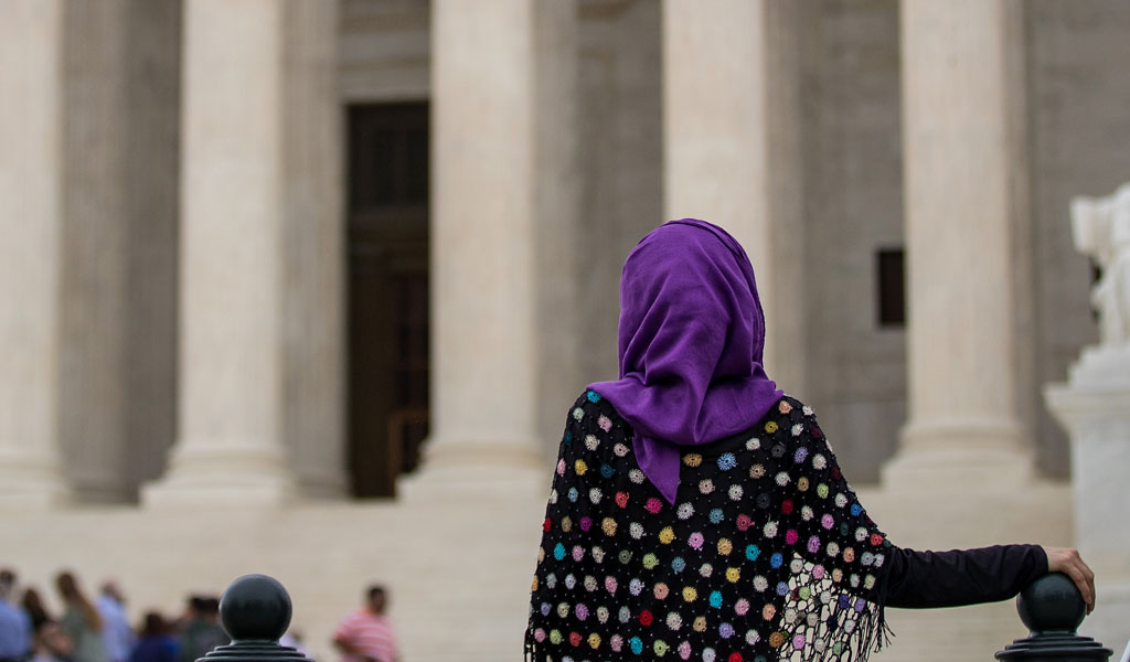 A woman wearing an Islamic head covering protests Trump's temporary travel ban in front of the U.S. Supreme Court