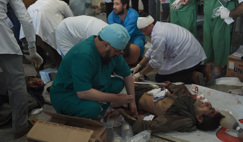 A doctor treats the wounded after 95 people were killed in an ambulance bomb. (Photo: WAKIL KOHSAR/AFP/Getty Images)
