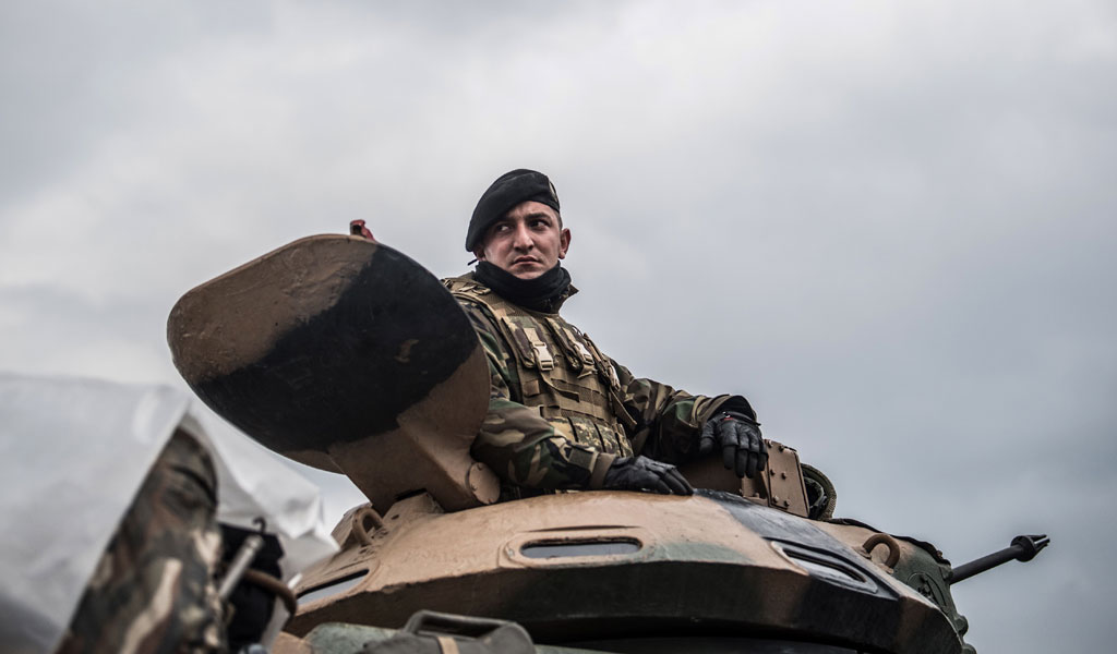 "A Turkish soldier in a tank waits on the border before invading the Afrin region of Syria in the ironically dubbed ""Operation Olive Branch"""