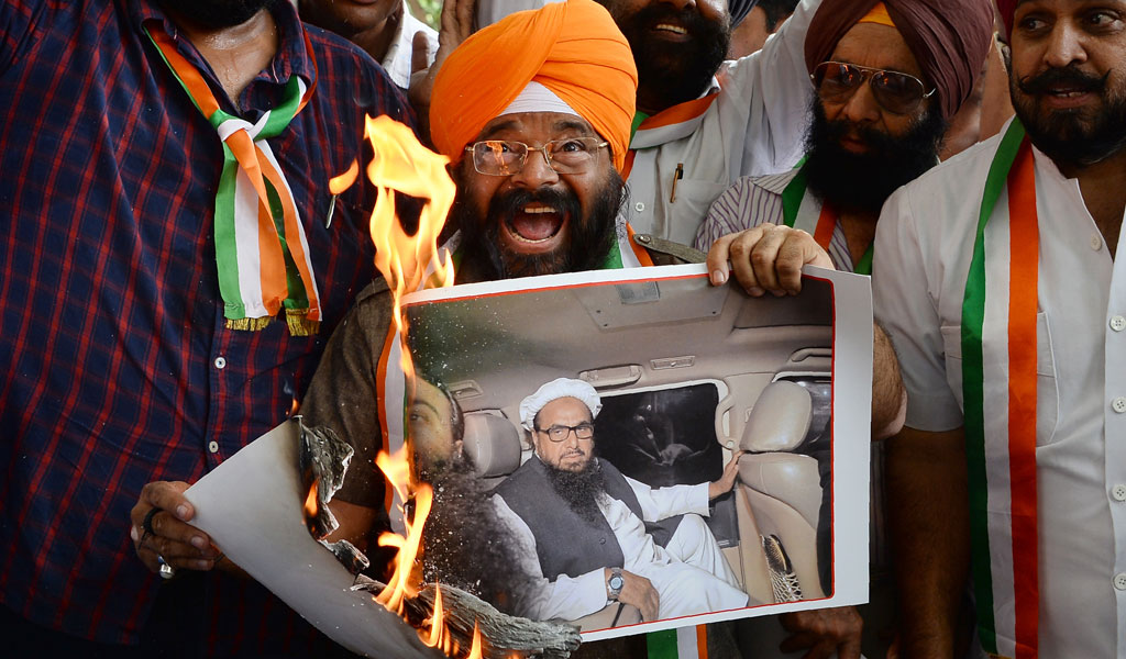 President of the National Akali Dal party, Paramjeet Singh Pamma burns a picture of arch-terrorist Hafiz Saeed, the mastermind behind the 2008 Mumbai terror attacks.