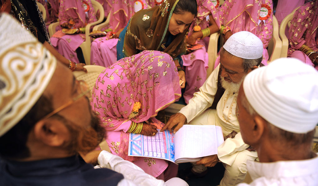A bride signs the certificate in a sharia marriage