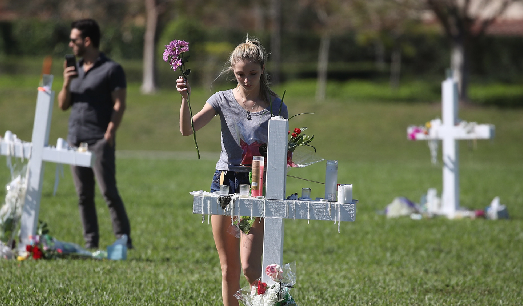 A young woman places flowers on a memorial after a mass shooting in Parkland, Florida. (Photo: Mark Wilson/Getty Images)