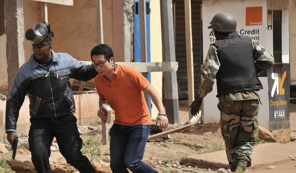 A rescued hostage is led away from the terror attack on the Raddison Blu hotel in Bamako, Mali (Photo: HABIBOU KOUYATE/AFP/Getty Images)