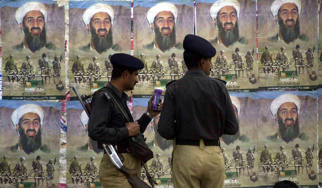 Pakistani policemen stand in front of posters of Osama bin Laden. Many Pakistanis protested when the US killed bin Laden in Pakistan (Photo: ARIF ALI/AFP/Getty Images)