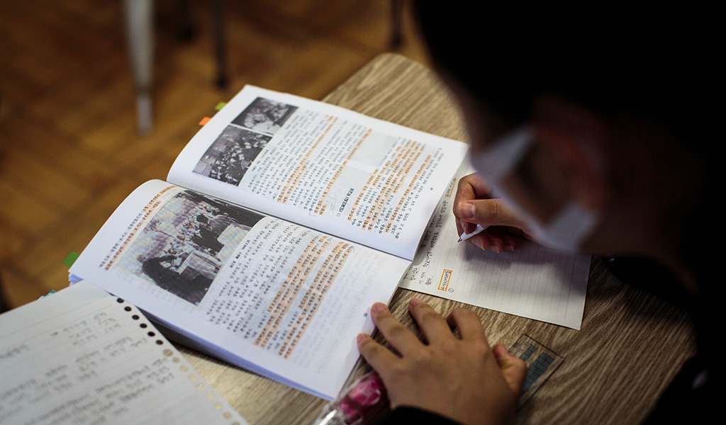 In this picture taken on October 13, 2017, a student takes notes from history book in a classroom at Tokyo Korean high school. (Photo: BEHROUZ MEHRI / AFP / Getty Images)