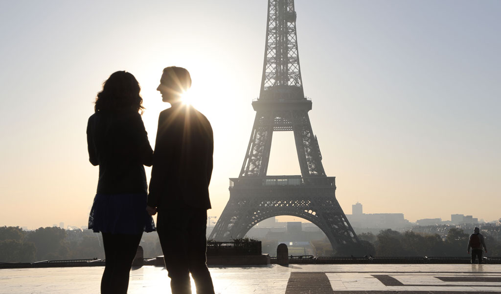 A couple in France in front of the Eiffel Tower (Illustrative photo: LUDOVIC MARIN/AFP/Getty Images)