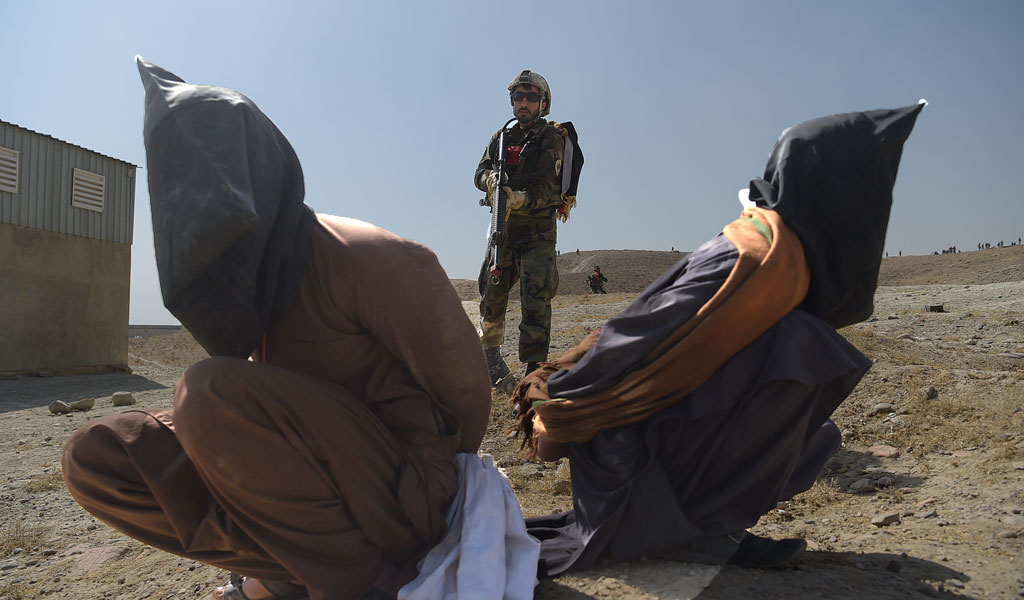 An Afghan soldiers on a training drill pretending to arrest Taliban militants (Photo: SHAH MARAI/AFP/Getty Images)