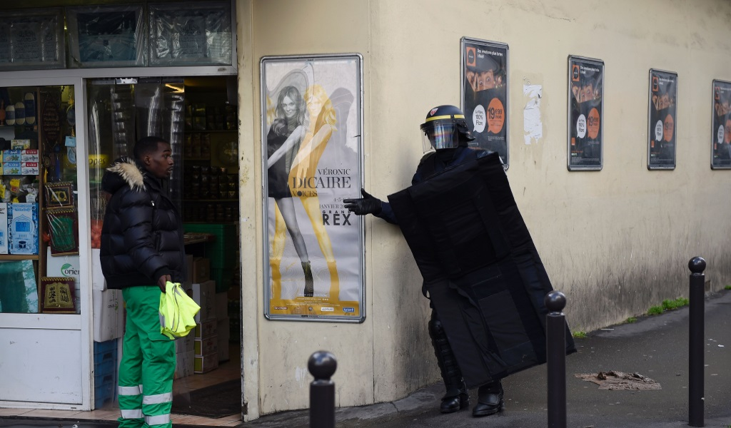 A French policeman speaks with a man about to enter shop near the Rue de la Goutte d'Or in the north of Paris on January 7, 2016, after police shot a man dead as he was trying to enter a police station. French police shot dead the knife-wielding man as he attacked a police station in Paris, a year to the day since jihadist gunmen killed 12 people at Charlie Hebdo newspaper. The man reportedly shouted 'Allahu Akbar' (God is Greatest) and was wearing what appeared to be an explosives vest although it was later found to be a fake, police and government sources said. (Photo: LIONEL BONAVENTURE / AFP / Getty Images)