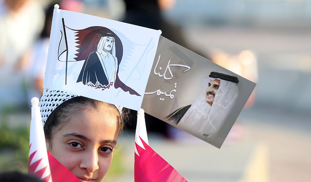 A Qatari girls wears flags bearing the portrait of the Emir of Qatar, Sheikh Tamim bin Hamad bin Khalifa al-Thani as Qataris gather in the streets of Doha to welcome back the emir upon his returned from his first trip abroad during the Gulf diplomatic crisis on September 24, 2017. (Photo: KARIM JAAFAR / AFP / Getty Images)