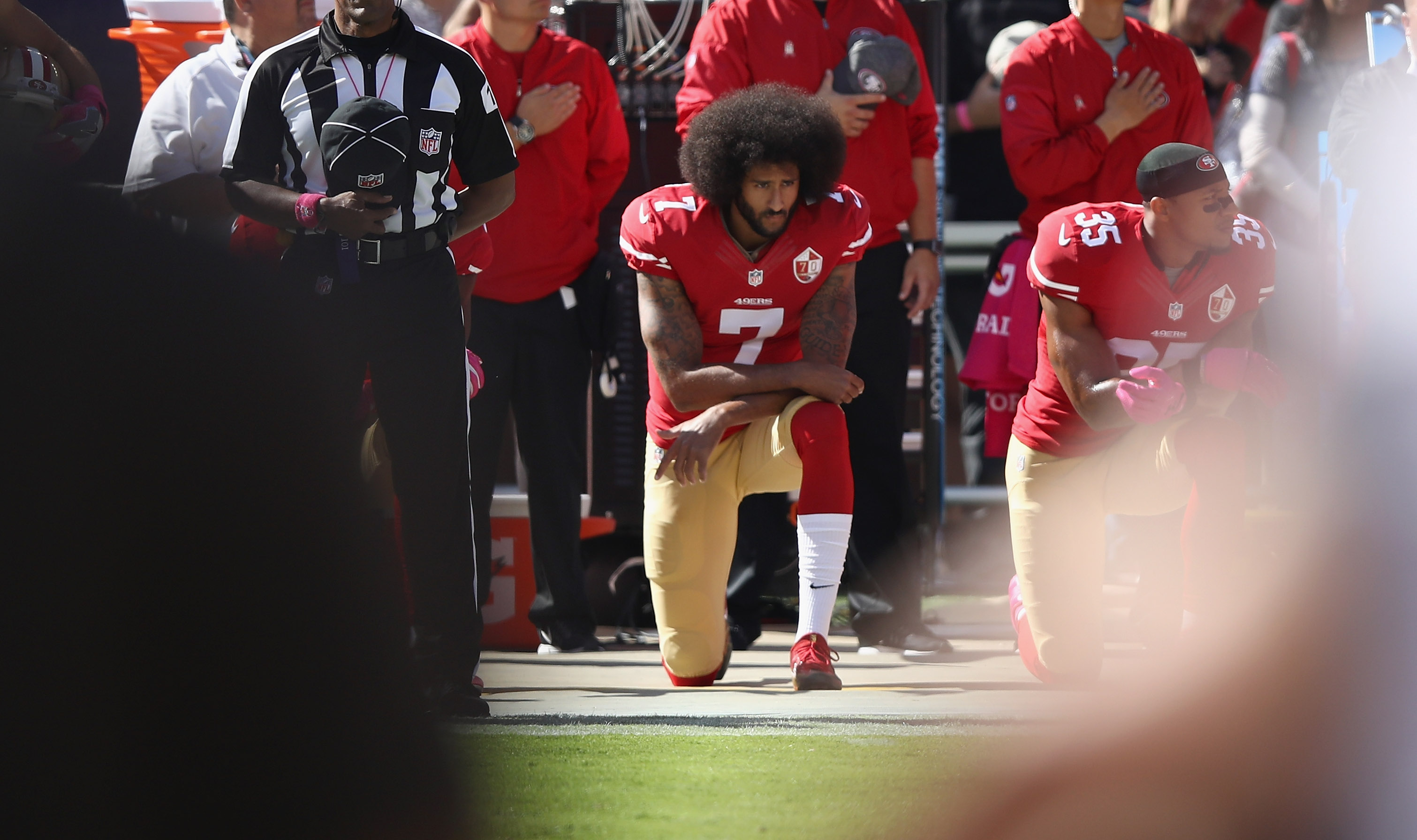Colin Kaepernick (#7) when he played for the San Francisco 49ers kneels for the national anthem (Photo by Ezra Shaw/Getty Images)