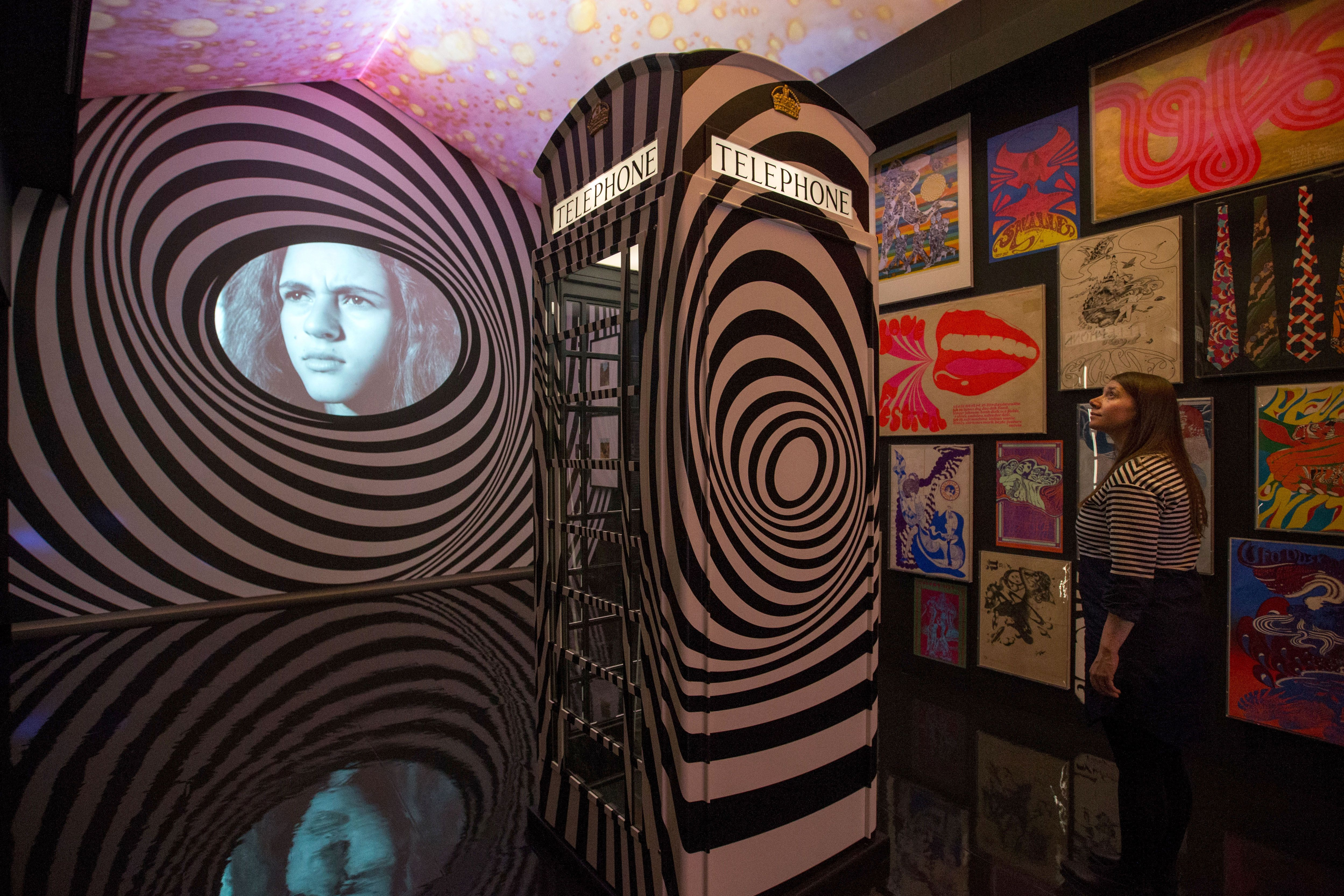 A member of staff poses at the 'Down the rabbit hole' room, featuring a telephone cabin, which was inspired by the famous psychedelic UFO club in London and English painter Bridget Riley's 1965 'Untitled' screen print of Plexiglas, during a photocall at the 'The Pink Floyd Exhibition: Their Mortal Remains' at the Victoria and Albert Museum in west London on May 9, 2017. (Photo: Daniel Leal-Olivas / AFP / Getty Images)