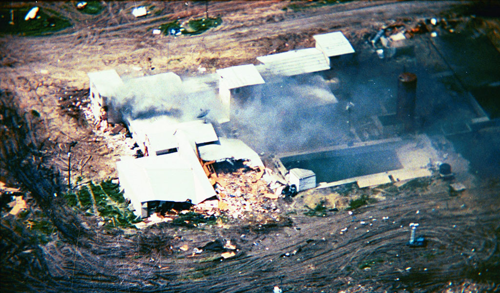 The Waco siege was the siege of a compound belonging to the Branch Davidians, carried out by American federal and Texas state law enforcement, as well as the U.S. military, between February 28 and April 19, 1993. The Branch Davidians were led by David Koresh and were headquartered at Mount Carmel Center ranch in the community of Axtell, Texas. (Photo: FBI / Wiki Commons - https://upload.wikimedia.org/wikipedia/commons/f/f5/Mountcarmelfire04-19-93-l.jpg)