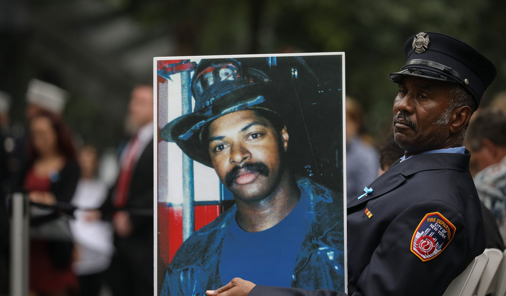 Retired New York City firefighter Bruce Stanley holds a portrait of his late friend Liam Smith Jr., a New York City firefighter who died in the 9/11 attacks, during a commemoration ceremony in New York City on Sept. 11, 2018 (Photo: Drew Angerer/Getty Images)