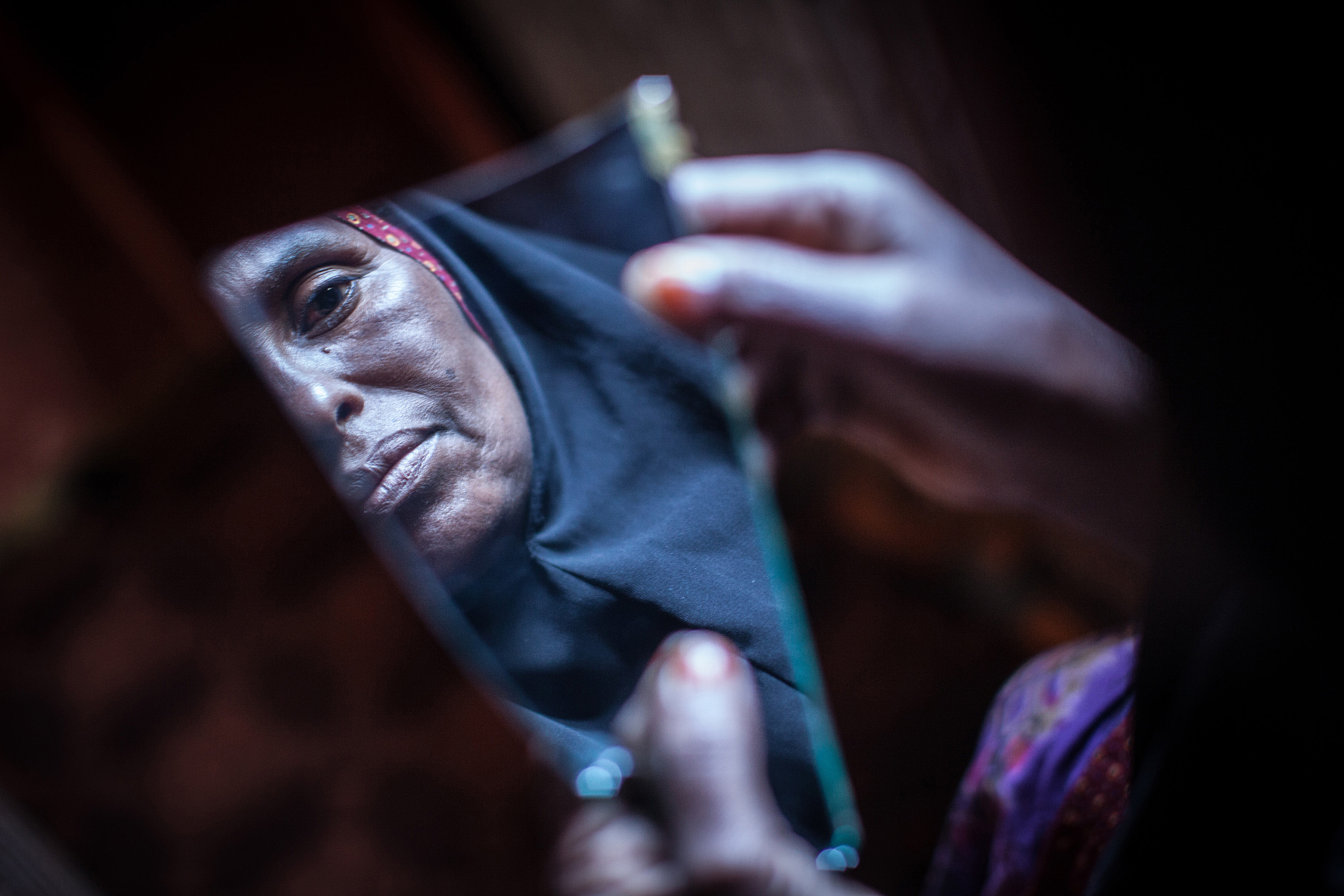 Somalia: A 'cutter' looks into a piece of a mirror. (Photo: Nichole Sobecki / AFP / Getty Images)