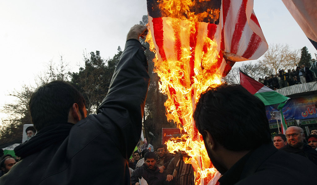 """Iranian hardline students burn a U.S. flag in 2009 to celebrate Hamas' """"victory"""" at the end of a three-week battle with Israel. (Photo: BEHROUZ MEHRI / AFP / Getty Images)"""