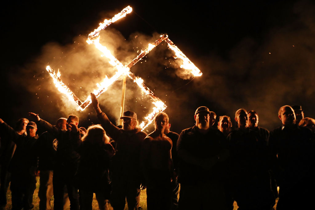 Members of the National Socialist Movement, one of the largest neo-Nazi groups in the US, hold a swastika burning after a rally on April 21, 2018 in Draketown, Georgia. (Photo: Spencer Platt / Getty Images)