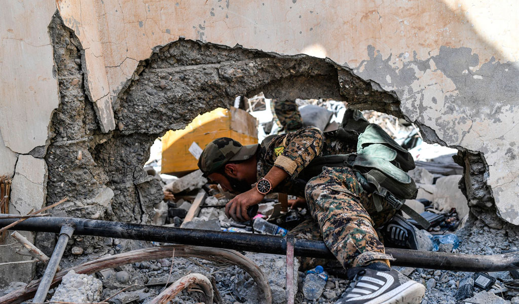 Members of the Syrian Democratic Forces (SDF), backed by US special forces, search a newly taken area near the central hospital of Raqa in October 2017. Raqa was the last remaining stronghold of ISIS (Photo: BULENT KILIC/AFP/Getty Images)