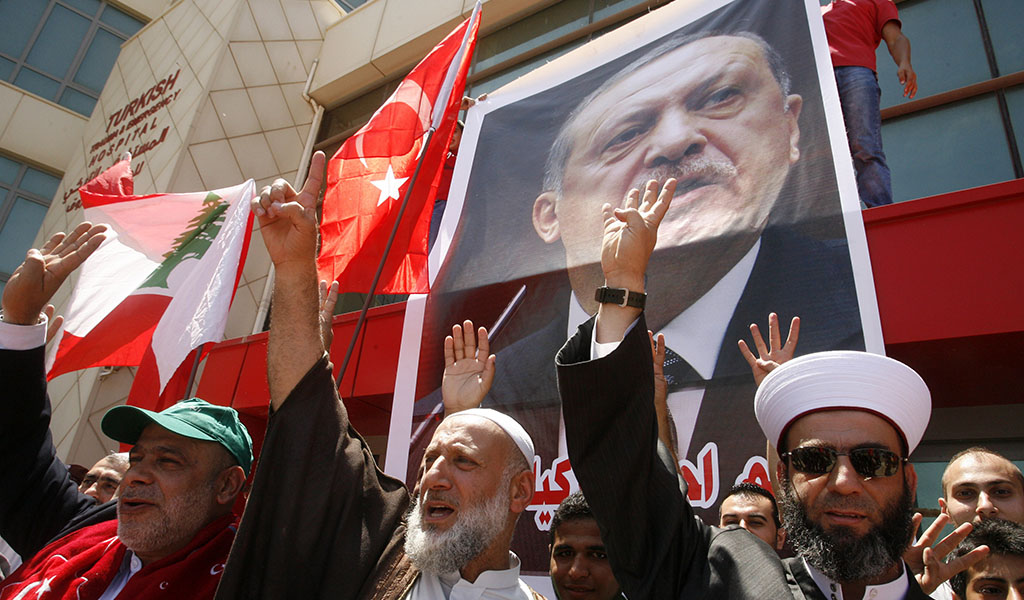 """Lebanese supporters and members of the Islamic group Jamaa Islamiya (some of them Shi'ite) wave Turkish and Lebanese flags and flash the four finger Muslim Brotherhood symbol known as """"Rabaa"""" during a demonstration to support Turkish President Recep Tayyip Erdogan (portrait) following a deadly but foiled coup attempt by an army faction on July 16, 2016 outside the Islamic Turkish hospital in the southern Lebanese port city of Sidon. (Photo: MAHMOUD ZAYYAT / AFP / Getty Images)"""