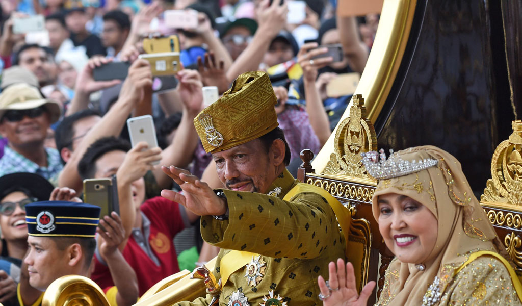 Brunei's Sultan Hassanal Bolkiah and Queen Saleha ride in a royal chariot during a procession to mark the sultan's golden jubilee of accession to the throne in October, 2017. (Photo: ROSLAN RAHMAN/AFP/Getty Images)