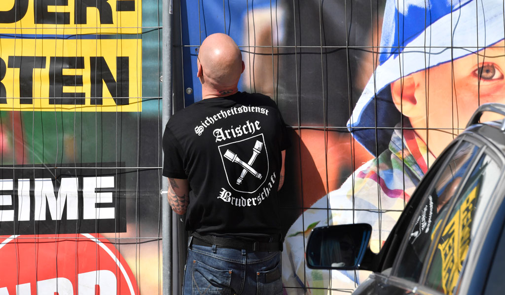 Private security personel with 'Aryan Brotherhood' on his T-shirt opens the gate at the venue of the Shield and Sword neo-nazi festival in the small eastern German town of Ostritz on April 20, 2018. (Photo: JOHN MACDOUGALL/AFP/Getty Images)