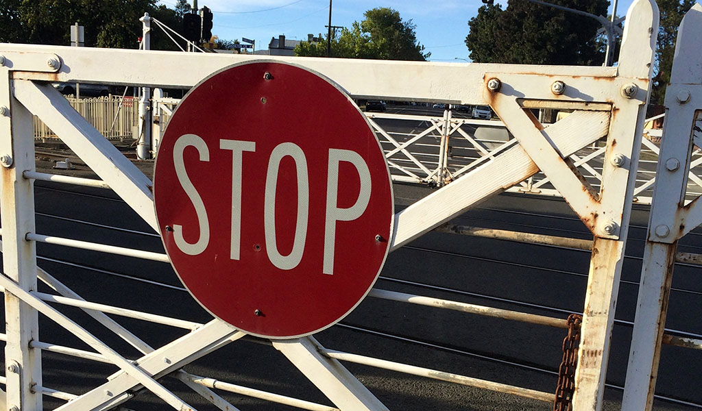 A stop sign on a boom gate (Truth Devour / Pexels)