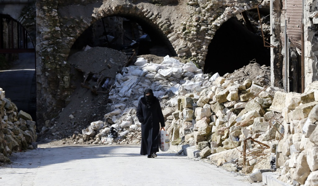 A woman walking past debris in the old quarter of Syria's second city of Aleppo on February 12, 2019. (Photo: LOUAI BESHARA / AFP / Getty Images)