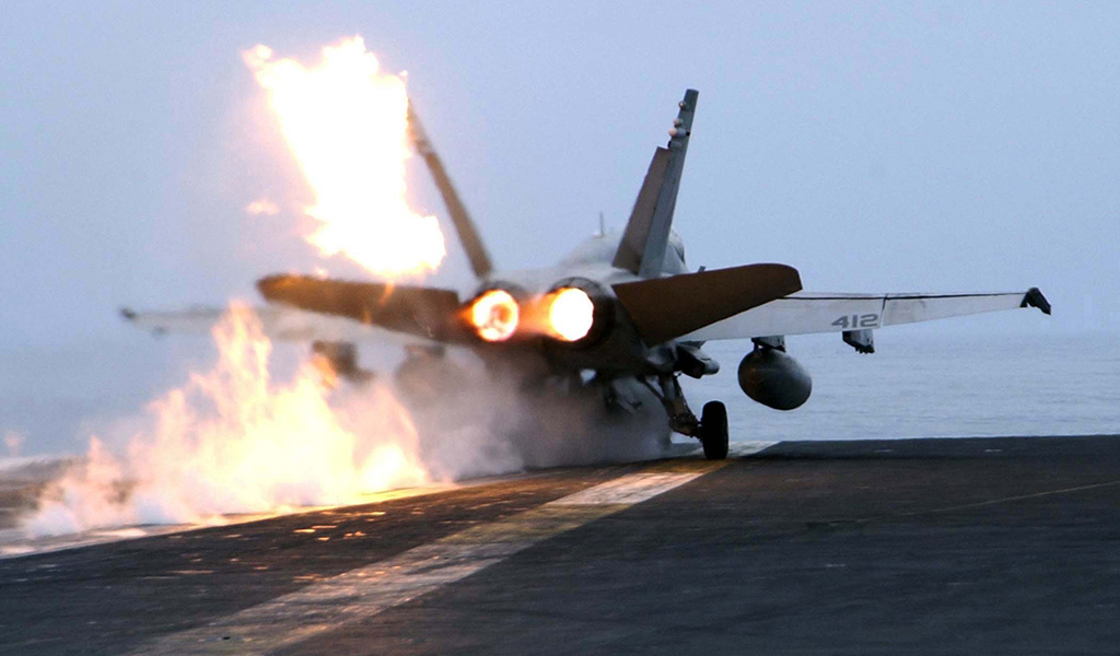A U.S. Marine Corps F/A-18C Hornet launches with after burners aglow from the flight deck of the aircraft carrier USS Abraham Lincoln (CVN 72) operating in the Pacific Ocean on Sept. 15, 2004. (Photo: Petty Officer 2nd class Philip A. McDaniel / U.S. Navy)