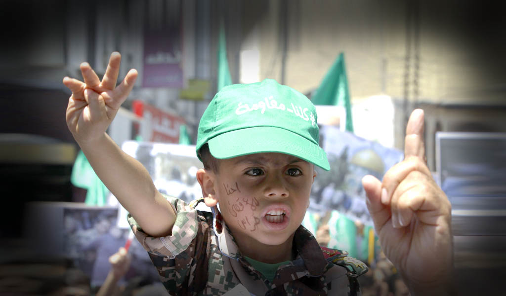 """A Jordanian boy in Amman in 2015 wearing a cap reading in Arabic, 'We are all resistance' takes part in a demonstration by Jordan's Muslim Brotherhood protest against Israeli """"violations"""" at Jerusalem's Al-Aqsa mosque, On his cheek is written, 'We are the guardians of Al-Aqsa.' (Photo: KHALIL MAZRAAWI/AFP/Getty Images)"""