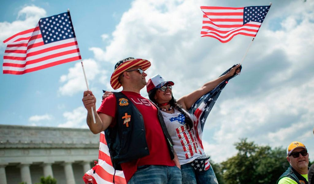 "A couple waves US flags at the ""Rolling Thunder"" parade in honor of missing American soldiers on Memorial Day weekend in Washington on May 26 2019. (Photo: ERIC BARADAT/AFP/Getty Images)"
