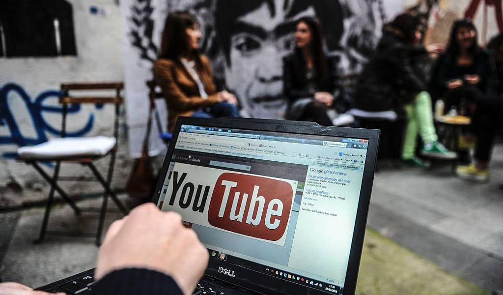 A laptop computer showing YouTube's logo on March 27, 2014 in Istanbul, near a poster of Berkin Elvan, the 15-year-old boy who died nine months after he was hit by a tear gas canister while going to buy bread during the 2013 protests in Istanbul. Turkey banned YouTube and Twitter after both were used to spread audio recordings implicating the prime minister in a huge corruption case. Is this where we are headed in the West? (Photo: OZAN KOSE/AFP/Getty Images)
