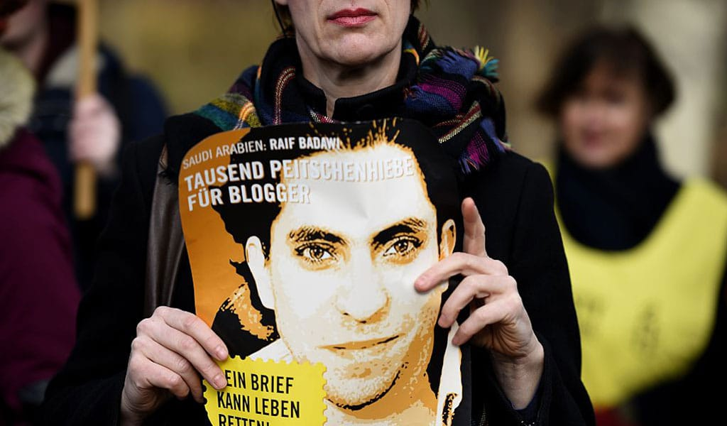 An Amnesty International activist holds a picture of Saudi blogger Raif Badawi during a protest against his flogging punishment in January 2015 in front of Saudi Arabia's embassy to Germany in Berlin. (Photo: TOBIAS SCHWARZ/AFP/Getty Images)