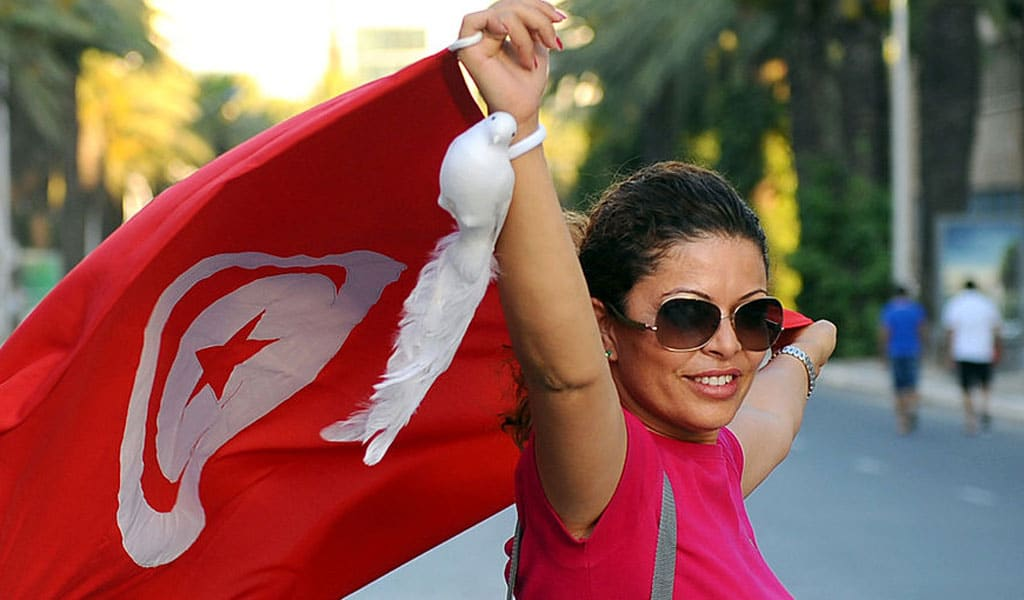 A Tunisian woman holds the national flag as she particiaates in a march against terrorism and Islamic extremism in Tunis on July 7, 2011. The demonstration came in the wake of the ransacking of a cinema by activists from a Salafist group. (Photo: FETHI BELAID/AFP/Getty Images)