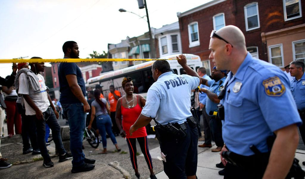 Police officers direct citizens to move back near the scene of a shooting August 14, 2019 in Philadelphia. Six police officers were wounded in an hours-long standoff with a gunman that prompted a massive law enforcement response in the city's Nicetown-Tioga neighborhood. (Photo: Mark Makela/Getty Images)